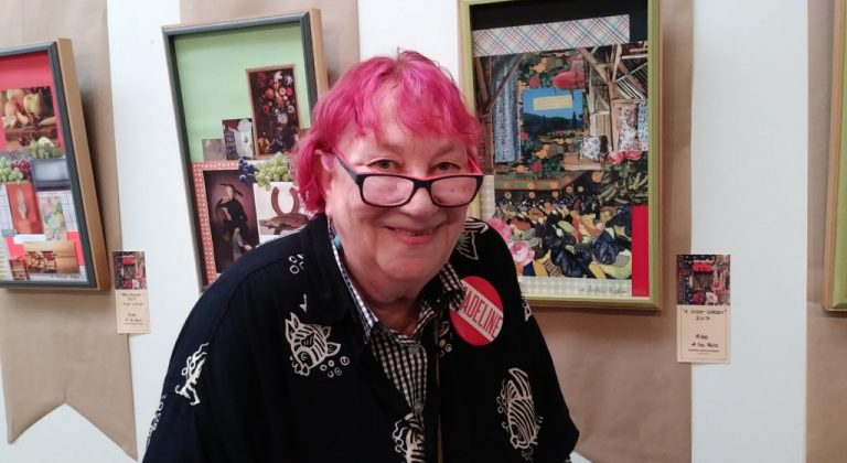 A resident, with dyed magenta hair, wearing glasses, standing in front of her art exhibition