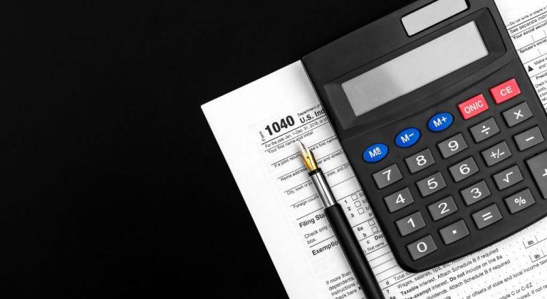 a tax form, a pen, and a calculator