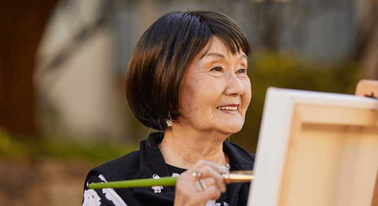 A resident painting on a canvas