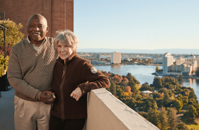two residents standing on a balcony smiling