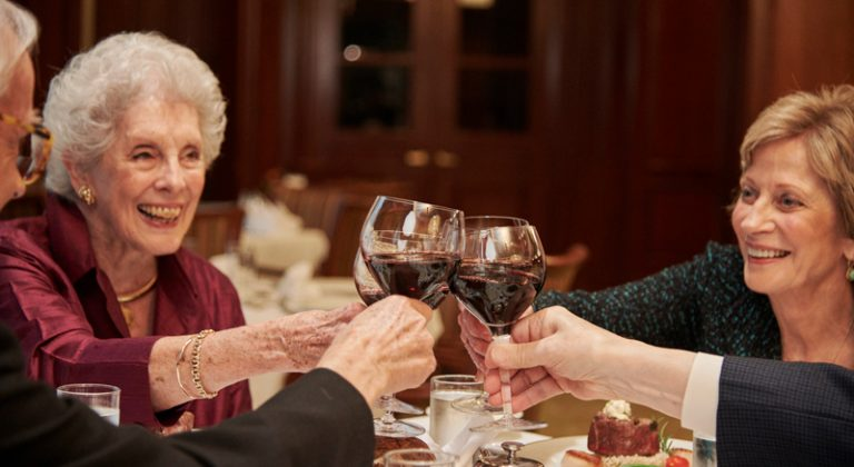 A group of four residents clink wine glasses filled with red wine