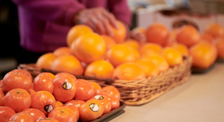 persimmons and tangerines in trays on a table. A woman's hand is reaching for a tangerine