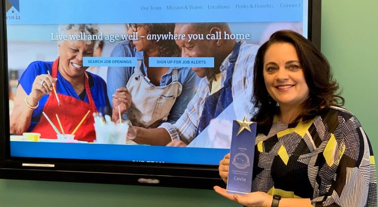 A person holds an award in front of a screen displaying a website