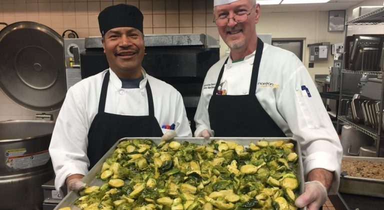 Chefs holding a tray of brussel sprouts