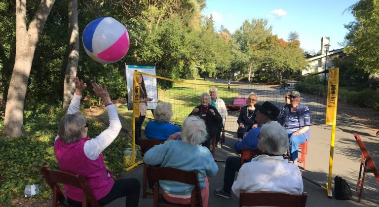 Residents sitting on chairs playing volleyball