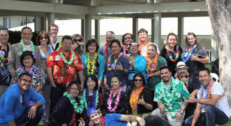 A group of Covia employees wearing Hawaiian shirts and leis