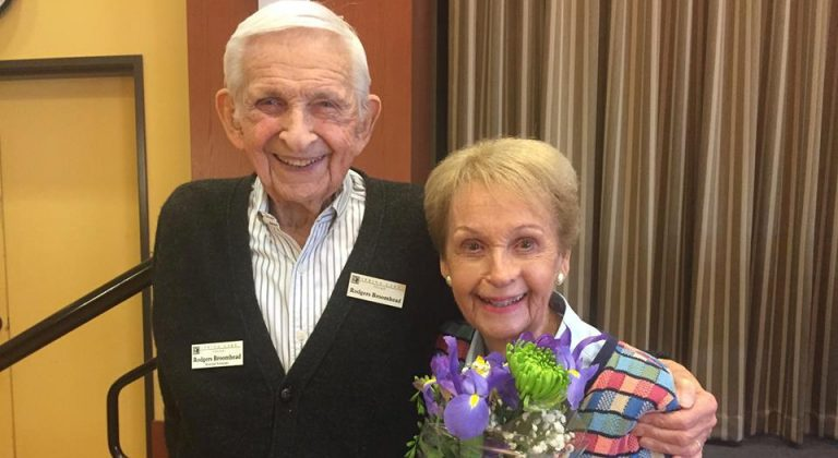 two residents standing together smiling