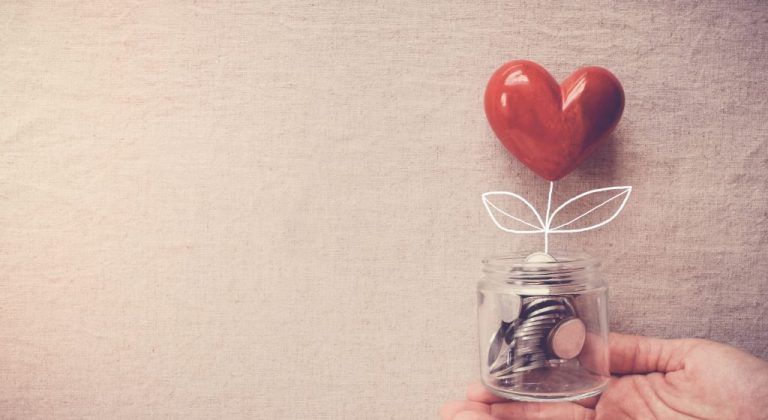 a hand holding a jar of coins with a red heart on top