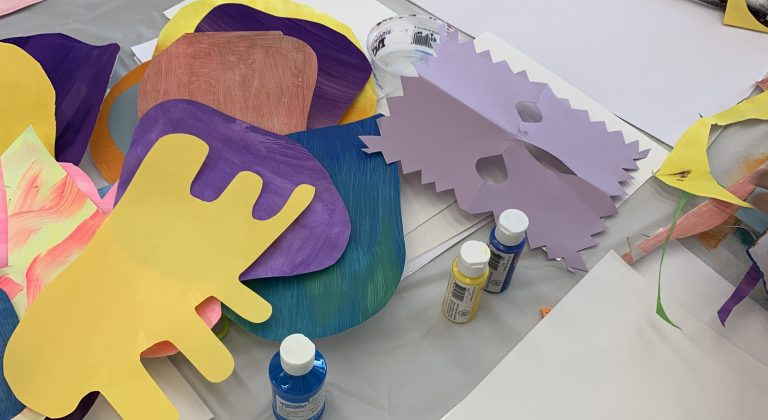 paper cut out into shapes and bottles of paint