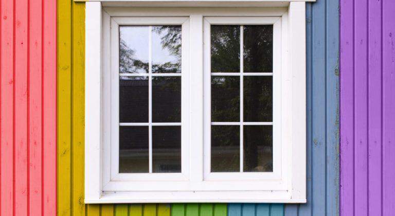 A window on a rainbow colored wall