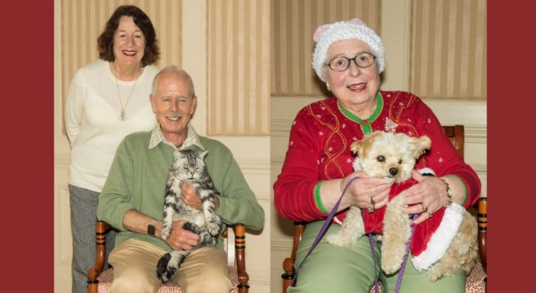 Two residents holding their pets. One is holding a cat, the other a dog.