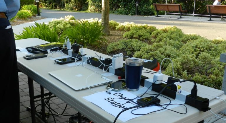 A charging station table with cell phones and a laptop plugged in