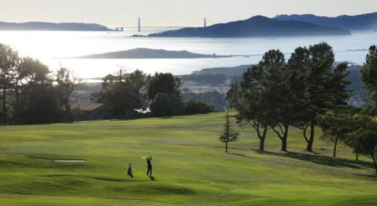 A gold course with a view of the Golden Gate Bridge in the background