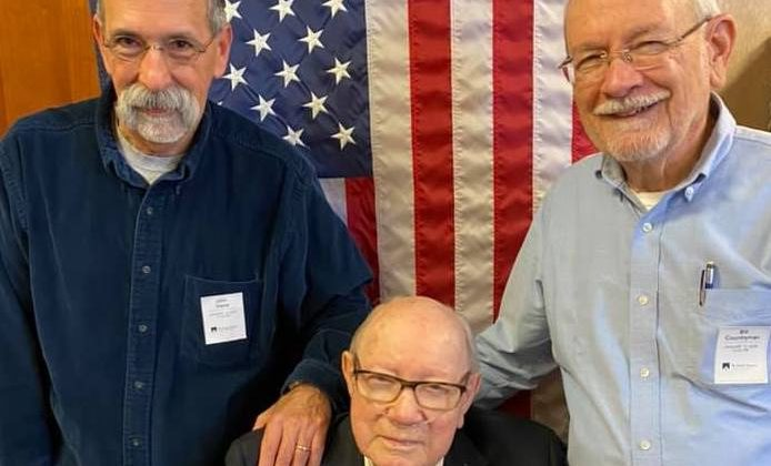 Three residents pose in front of the USA flag.