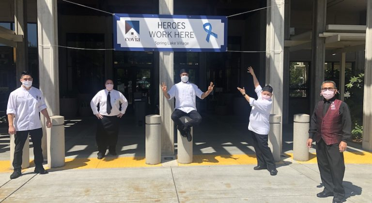 """Covia employees standing in from of a """"Heroes Work Here"""" sign"""