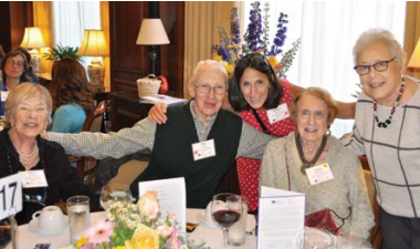 A group of five residents pose for a photo at a banquet table.