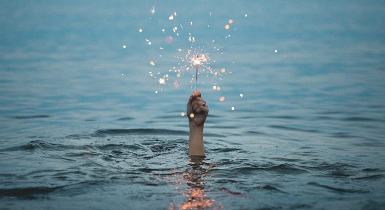 A hand holding a sparkler comes out of a large body of water