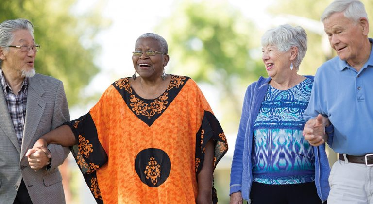 Four older adults laugh together outside