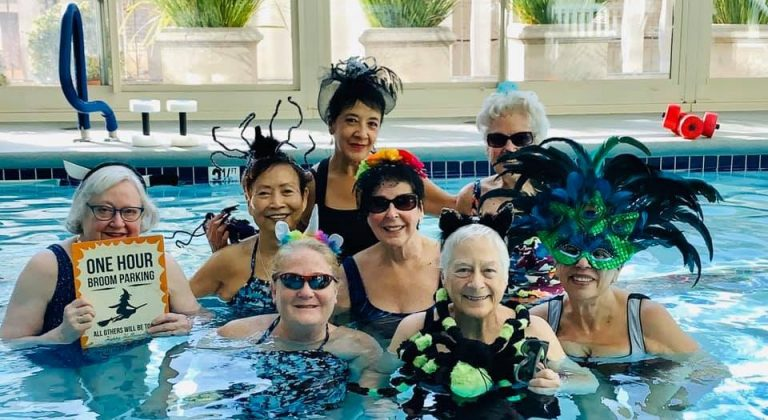 The San Francisco Towers water aerobics class stands in the pool in Halloween attire