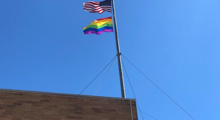 A Pride flag and a US flag fly on the top of St. Paul's Towers